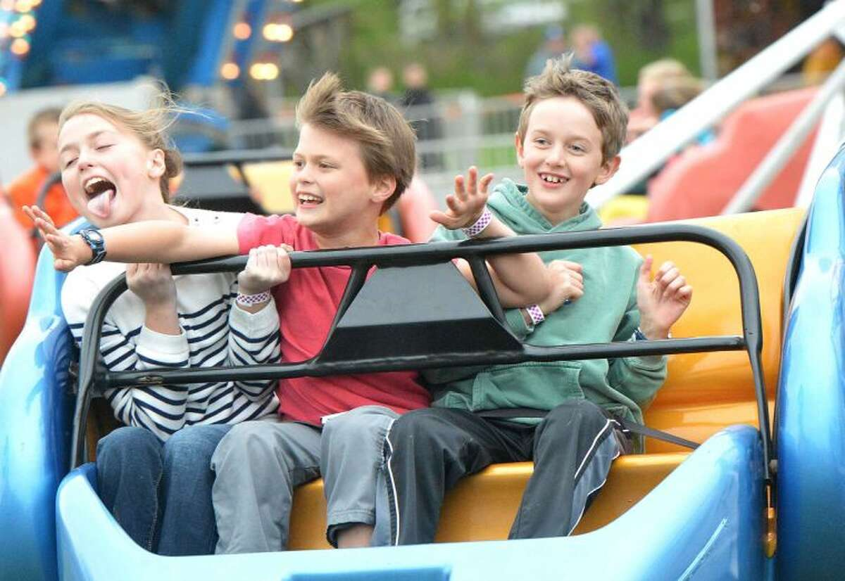 Hour Photo/Alex von Kleydorff Phoebe Naylor , Henry Naylor and Alexander Fortuna take a ride on the scrambler during opening night at the Rowayton Carnival