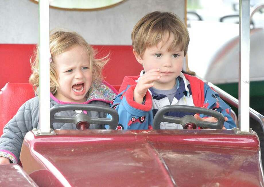 Hour Photo/Alex von Kleydorff Carys Rader is unsure of her older brother Henry's driving as the two set off on the roudabout cars at The Rowayton carnival on Friday Night