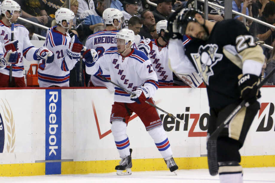 New York Rangers' Ryan McDonagh, center, celebrates with teammates as he returns to the bench after his goal in the second period of Game 5 of a second-round NHL playoff hockey series as Pittsburgh Penguins' Craig Adams (27) heads back to his bench in Pittsburgh Friday, May 9, 2014. (AP Photo/Gene J. Puskar)