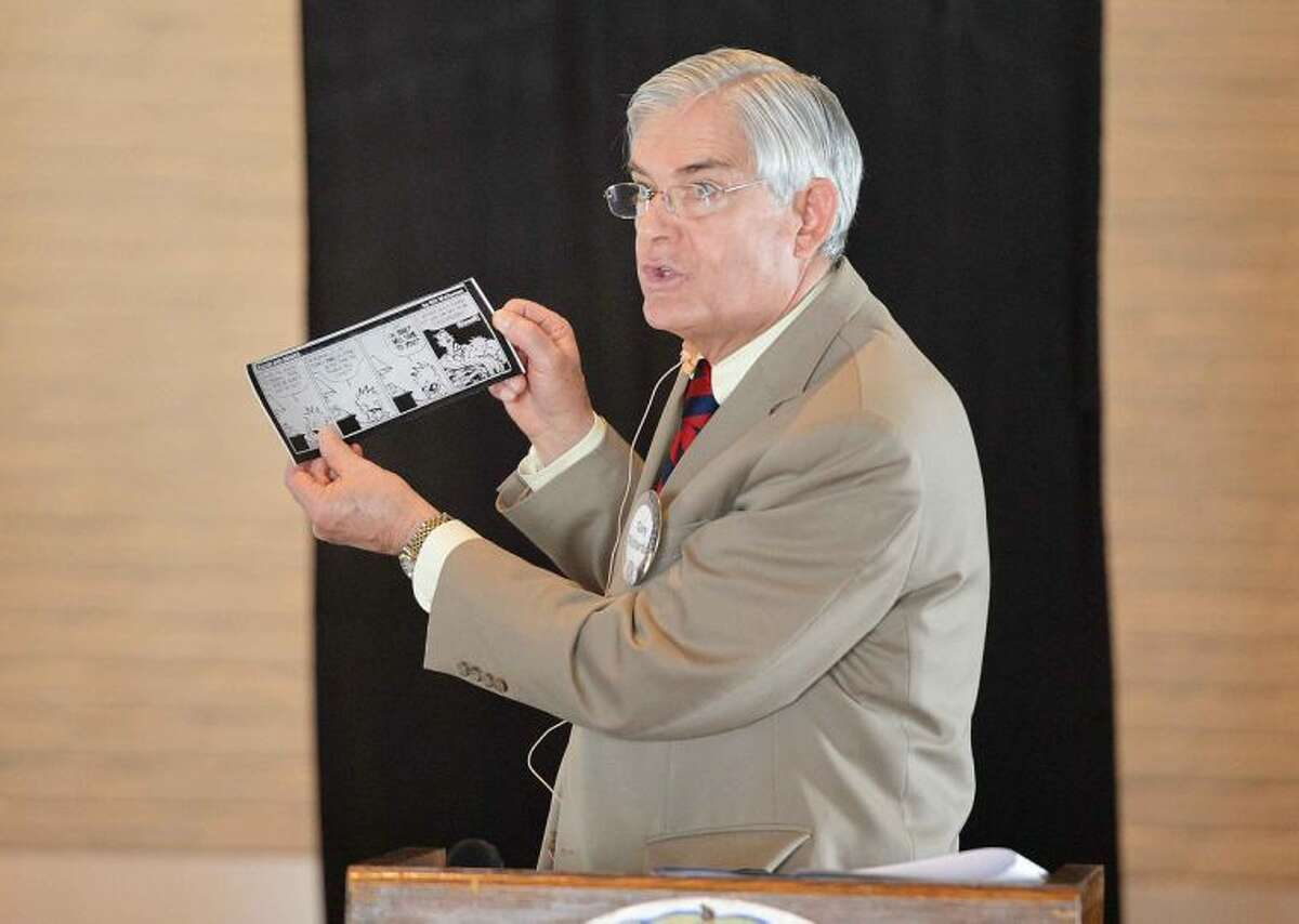 Outgoing Superintendent of Schools Dr. Gary Richards reads a Calvin and Hobbs comic strip that pokes fun at 'snow days' as he speaks to the Wilton Kiwanis Club.