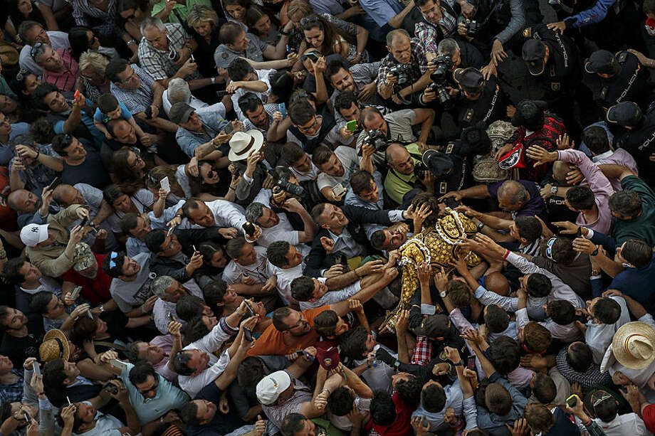 French bullfighter Sebastian Castella is carried on the shoulders and greeted by supporters as he leaves the bullring after an extraordinary performance during a bullfight of the San Isidro fair Madrid, Spain, Wednesday, May 27, 2015. Only after extraordinary performances bullfighters are allowed to be carried on the shoulders of supporters. San Isidro's bullfighting fair is one of the most important in the world. Bullfighting is an ancient tradition in Spain. (AP Photo/Daniel Ochoa de Olza)