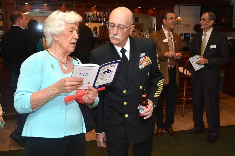 Hour Photo/Alex von Kleydorff Port 5 Commander Rich Iannucci looks over the program with Joanne Fabry during the ABRI/Homes for The Brave Salute 2014 Gala at the St Ann Club