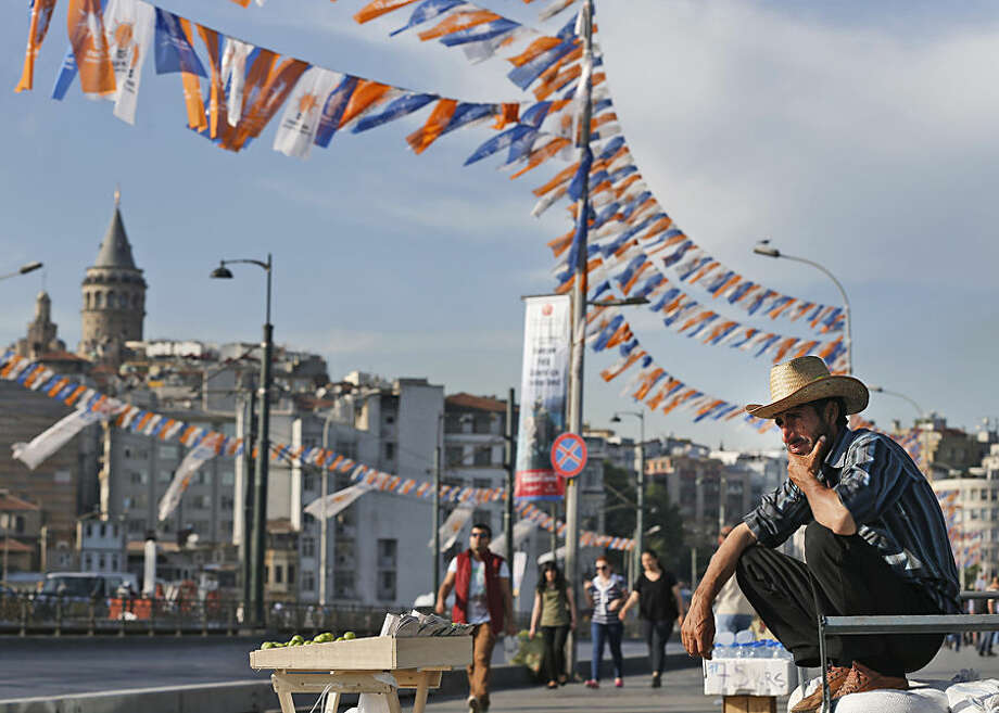 A street vendor is backdropped by the iconic Galata Tower and party flags and banners for the upcoming elections, as he waits for customers, in Istanbul, Turkey, Tuesday, May 26, 2015. Turkey will hold general election on June 7, 2015 and approximately 56 million Turkish voters are eligible to cast their ballots to elect the 550 members of national parliament. (AP Photo/Emrah Gurel)