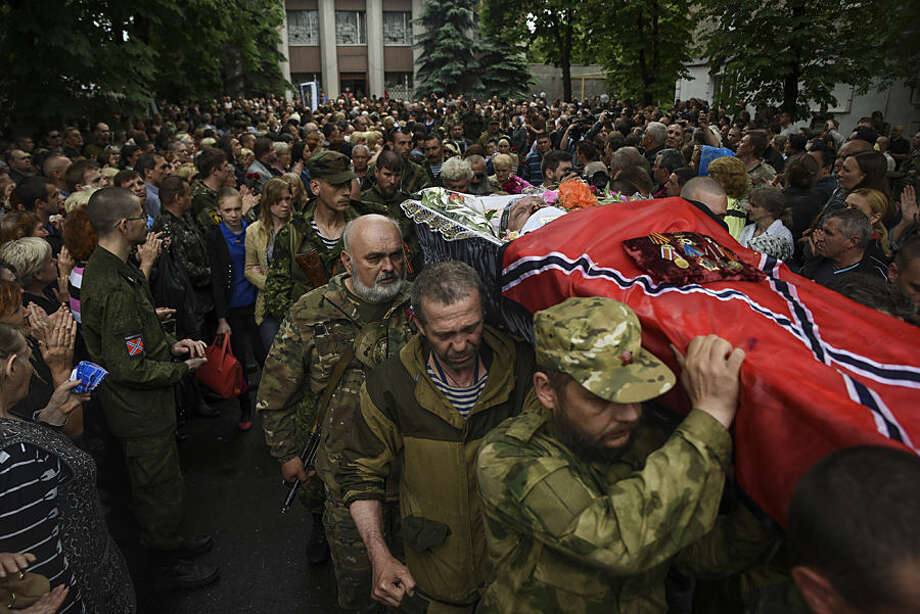 Pro-Russia rebels carry a coffin with the body of prominent separatist commander Alexei Mozgovoi during his funeral in Alchevsk, Ukraine, Wednesday, May 27, 2015. Alexei Mozgovoi and at least six other people were killed on Saturday in eastern Ukraine when his vehicle was ripped apart by a bomb and then strafed by gunfire. (AP Photo/Mstyslav Chernov)