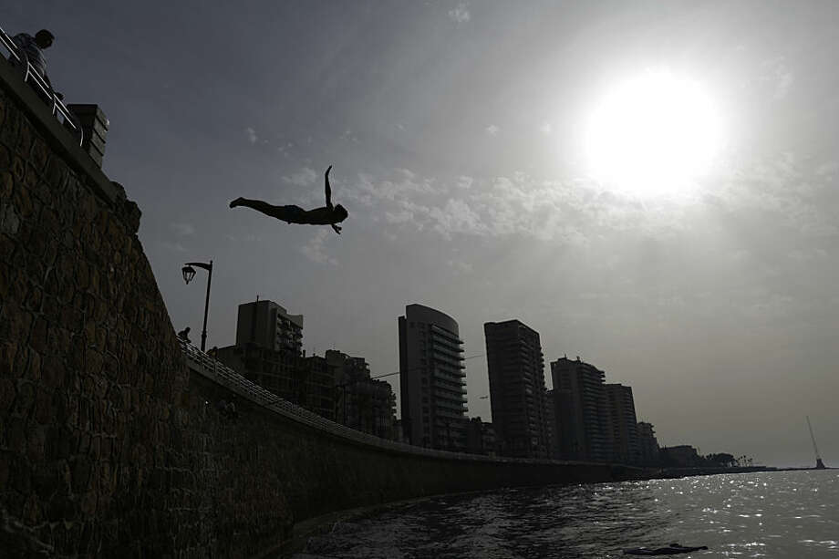 A youngster jumps into the Mediterranean Sea on the Beirut coastline, Lebanon, Wednesday, May 27, 2015. (AP Photo/Hassan Ammar)