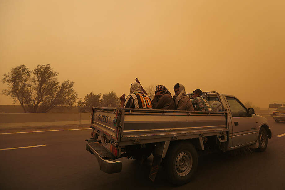 Laborers cover their faces as they ride a truck on a highway in Cairo, Egypt, Wednesday, May 27, 2015, during a sandstorm and a heat wave. Temperatures are soaring across the Middle East, with winds and sandstorms driving people indoors as unlucky pedestrians try to shield themselves from the sun with books, newspapers or anything they can find. (AP Photo/Mosa'ab Elshamy)