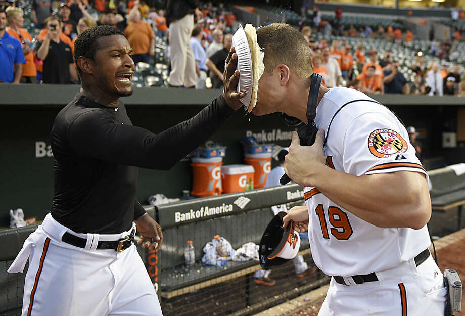 Baltimore Orioles' Adam Jones, left, throws a pie in the face of teammate Chris Davis after the Orioles' baseball game against the Houston Astros, Wednesday, May 27, 2015, in Baltimore. Davis hit two home runs, including a go-ahead solo shot in the eighth inning, as the Orioles won 5-4. (AP Photo/Nick Wass)