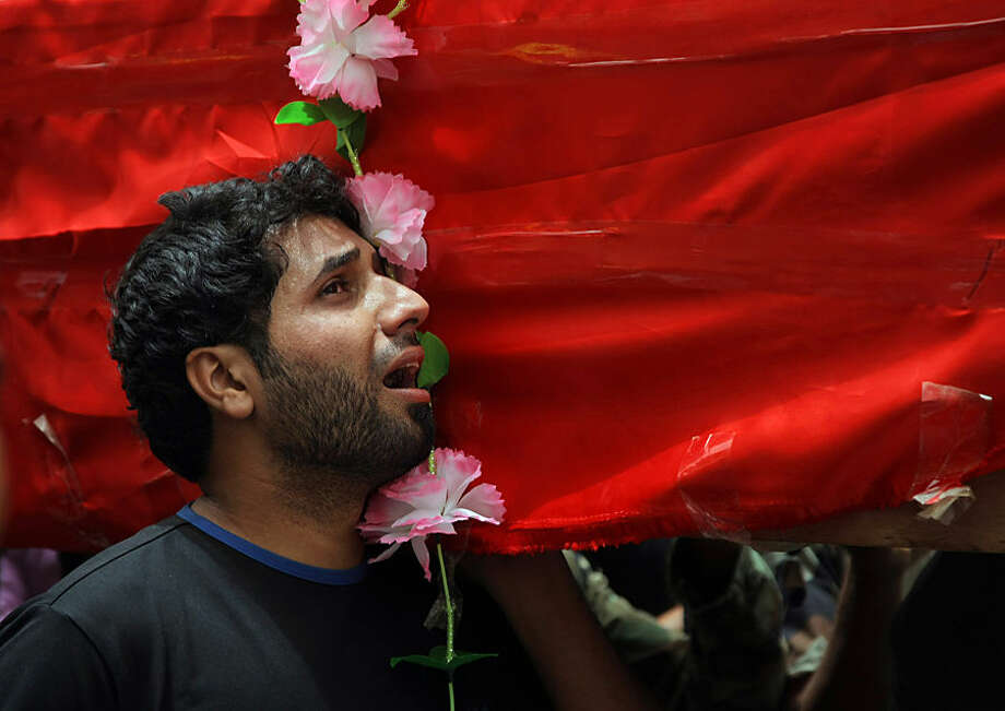 Mohammed Hussein mourns as he carries the flag-draped coffin of his brother during the funeral procession of three members of Peace Brigades, a Shiite militia group loyal to Shiite cleric Muqtada al-Sadr who were killed in Ramadi during fighting with Islamic State militants yesterday, their families said, in Najaf, 100 miles (160 kilometers) south of Baghdad, Iraq, Wednesday, May 27, 2015. (AP Photo/Jaber al-Helo)