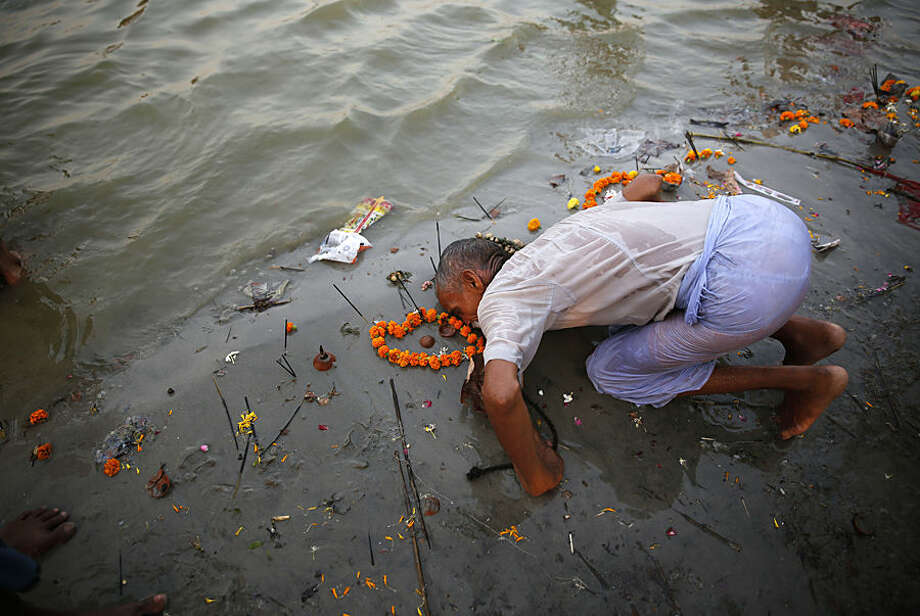 An elderly Hindu devotee offers prayers at Sangam, the confluence of the Rivers Ganges, Yamuna and the mythical Saraswati, in Allahabad, India, Thursday, May 28, 2015. Hindus across the country are celebrating Ganga Dussehra, devoted to the worship of the River Ganges. (AP Photo/Rajesh Kumar Singh)