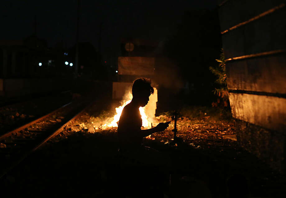 Filipino Juanito Bandong uses his smartphone beside a bonfire along the railroad tracks in Manila, Philippines, Wednesday, May 27, 2015. Bandong and his family lived for years beside the railroad tracks until they were evicted by the government and placed at a relocation site in Cavite province. He returns to Manila for work and sleeps beside the tracks near the location of his former home. (AP Photo/Aaron Favila)