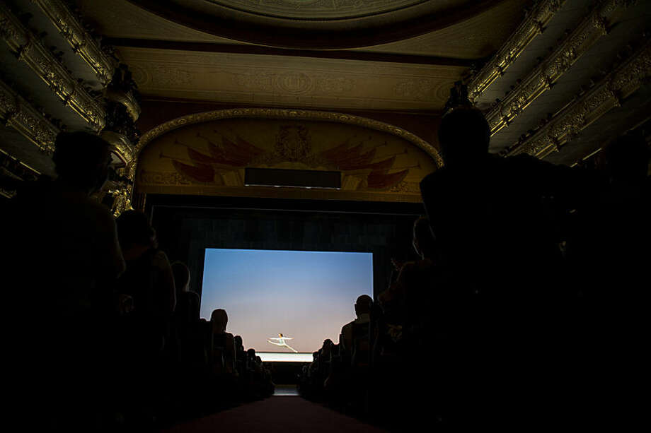 Spectators watch as the Bolshoi Theater soloist Semyon Chudin performs, choreographed by George Balanchine, during a Gala Concert in the Bolshoi Theater in Moscow, Russia, Wednesday, May 27, 2015. (AP Photo/Pavel Golovkin)