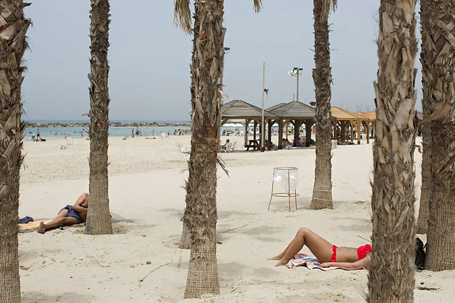 Israelis and tourists relax on the beach in Tel Aviv, Israel, Wednesday, May 27, 2015. Israel is experiencing a heat wave with temperatures reaching about 42 degrees Celsius (107.6 degrees Fahrenheit) in Tel Aviv. (AP Photo/Oded Balilty)