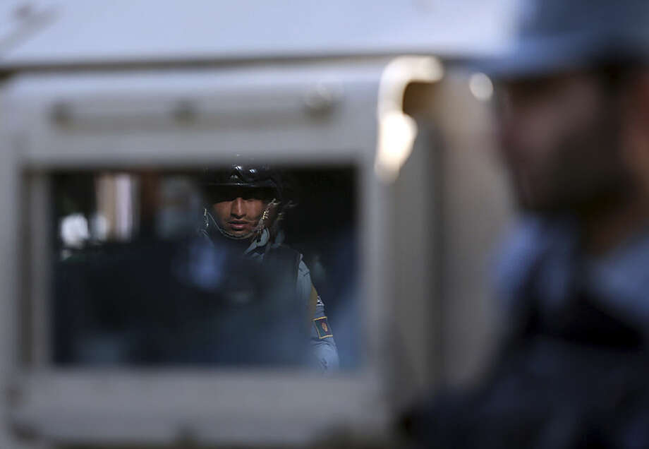 Afghan security officers stand guard near a guesthouse targeted in an overnight attack by the Taliban, in Kabul, Afghanistan, Wednesday, May 27, 2015. An all-night siege in an upscale neighborhood of Afghanistan's capital ended in the early hours of Wednesday morning with the deaths of four heavily armed Taliban attackers, though no civilians or security personnel were injured or killed, an Afghan official said. (AP Photo/Rahmat Gul)