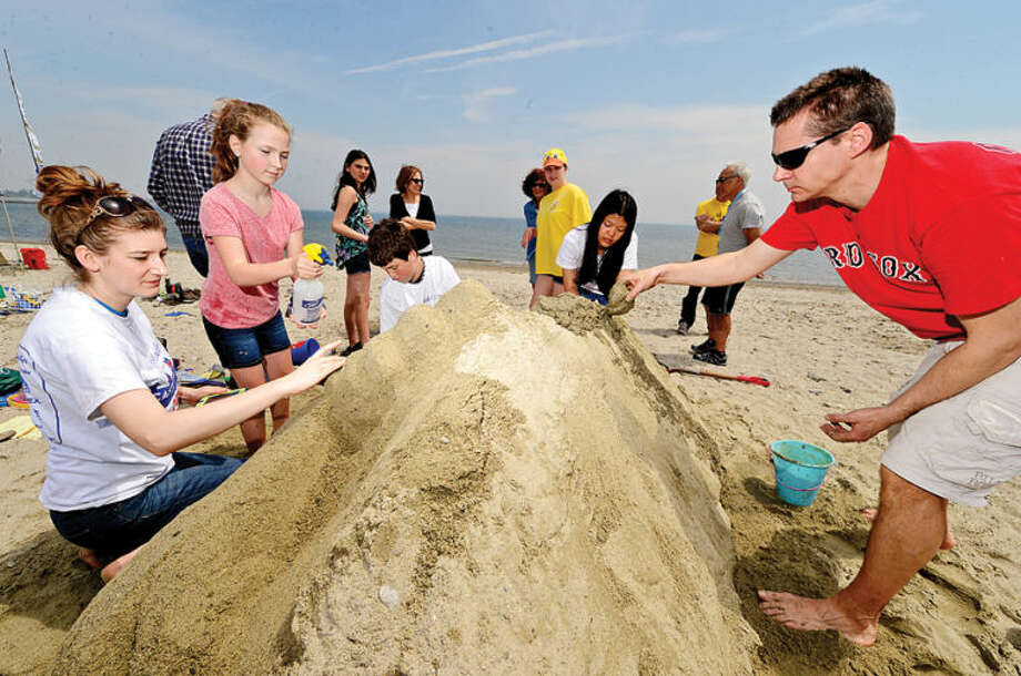 Hour photo / Erik Trautmann Teams compete in the Homes with Hope 13th annual Castles in the Sand sandcastle build-a-thon at Compo Beach in Westport on Saturday.