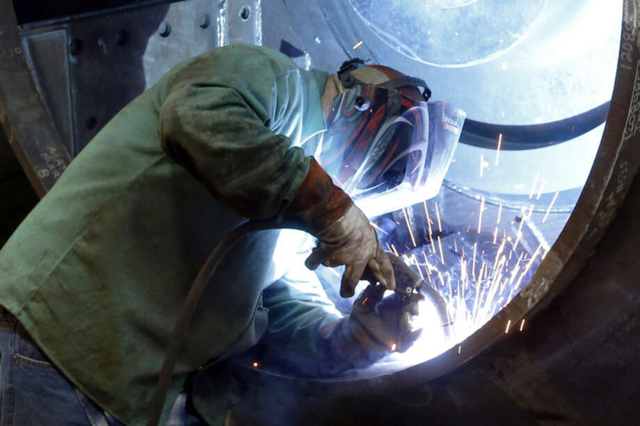 In this photo made on Thursday, Feb. 12, 2015, a man welds parts in fans for industrial ventilation systems at the Robinson Fans Inc. plant in Harmony, Pa. On Friday, the government will likely say the economy shrank in the January-March quarter for a second straight year, but steady job gains are widely expected to propel modestly healthy growth for the rest of 2015. (AP Photo/Keith Srakocic)