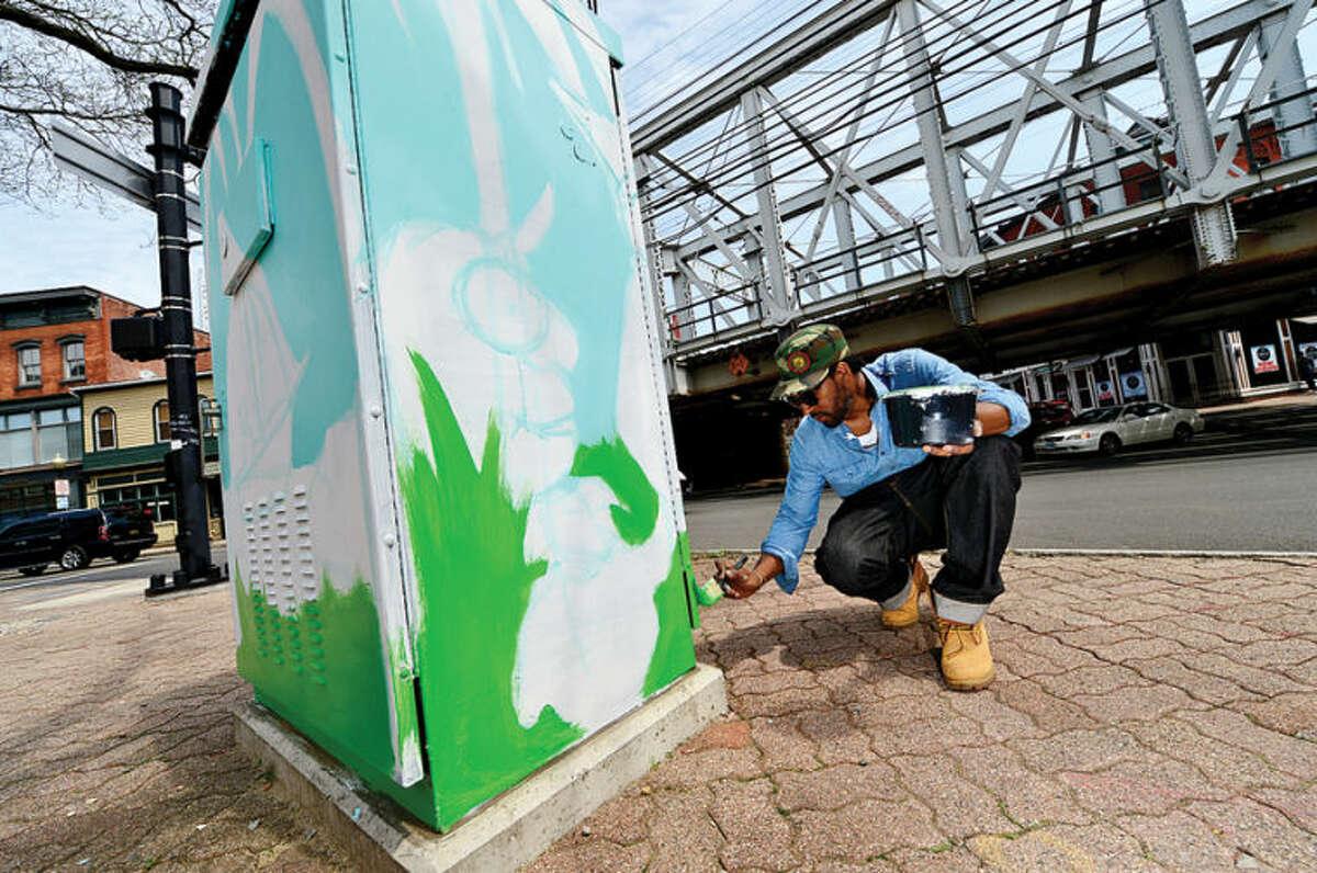 Hour photo / Erik Trautmann Norwalk artist Jahmane paints an electrical box along Washington St as part of the Urban Art program which transforms traffic boxes along city streets in South Norwalk.