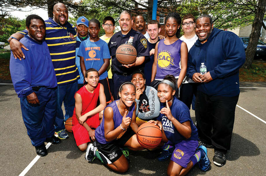 Hour photo / Erik Trautmann Norwalk police officer Hector Delgado, center, has organized a Police Athletic Association basketball league for the middle schoolers in the community.