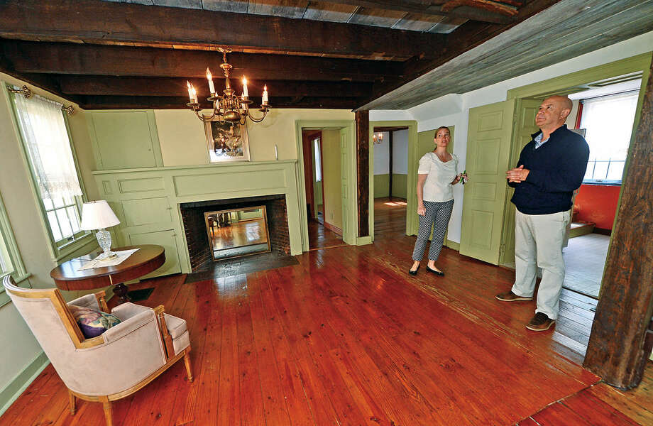 Real estate agents Heather Simmon and Rob Grodman look through the home at 44 Adams Avenue in Norwalk, Conn on Tuesday, May 10, 2016 which is for sale $399,000 and features some original flooring and hand-hewn beams. The Adams Avenue house is one of only a handful of homes to survive the Burning of Norwalk during the Revolutionary War.