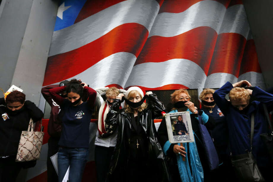 Family members of victims of the Sept. 11, 2001 attacks tie black gags over their mouths in protest of the transfer of unidentified remains of those killed at the World Trade Center from the Office of the Chief Medical Examiner to the World Trade Center site, Saturday, May 10, 2014, in New York. The remains will be transferred to an underground repository in the same building as the National September 11 Memorial Museum. (AP Photo/Jason DeCrow)