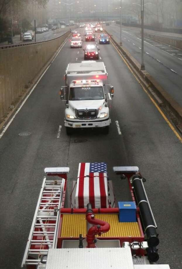 An American flag is draped over a casket of the unidentified remains of victims of the Sept. 11, 2001 attacks as they are returned to the World Trade Center site, Saturday, May 10, 2014, in New York. The remains were moved from the Office of the Chief Medical Examiner on Manhattan's East Side at dawn Saturday to an underground repository in the same building as the National September 11 Memorial Museum. (AP Photo/Julio Cortez)