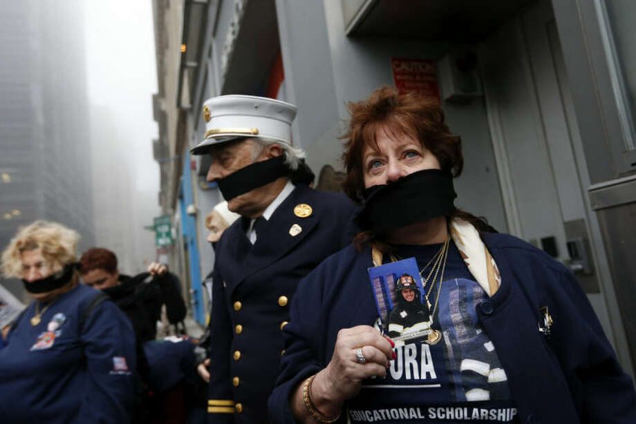 Maureen Santora holds a photo of her son, firefighter Christopher Santora, as she and other family members of victims of the of the Sept. 11, 2001 attacks wear black gags over their mouths in protest of the transfer of unidentified remains of those killed at the World Trade Center from the Office of the Chief Medical Examiner to the World Trade Center site, Saturday, May 10, 2014, in New York. The remains will be transferred to an underground repository in the same building as the National September 11 Memorial Museum. (AP Photo/Jason DeCrow)