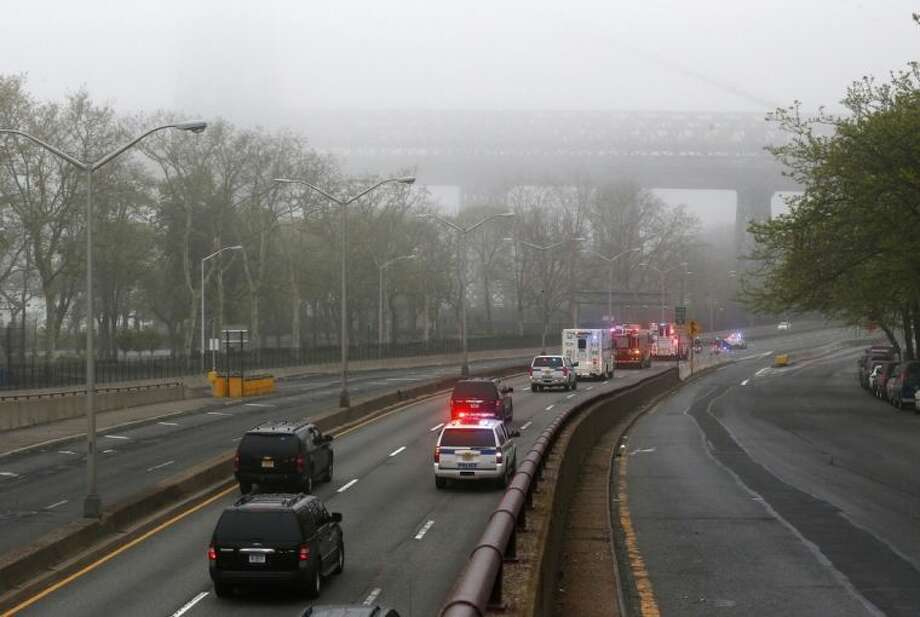 Part of the Williamsburg Bridge peeks through thick morning fog as police and fire department vehicles lead a procession along Franklin D. Roosevelt East River Drive with the unidentified remains of victims of the Sept. 11, 2001 attacks as they are returned to the World Trade Center site, Saturday, May 10, 2014, in New York. The remains were moved from the Office of the Chief Medical Examiner on Manhattan's East Side at dawn Saturday to an underground repository in the same building as the National September 11 Memorial Museum. (AP Photo/Julio Cortez)