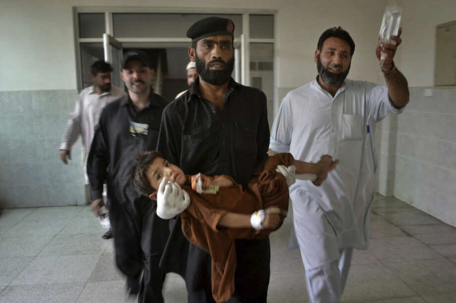A security guard carries an injured child after a bomb explosion at Lady Reading Hospital in Peshawar, Pakistan, Sunday, May 11, 2014. A police official in Pakistan says a bomb blast targeting refugees registering with the government has killed several people in northwestern city of Peshawar. Faisal Mukhtar says the bombing Sunday on a soccer field also wounded many people. He says it happened as officials registered refugees from the nearby Khyber tribal region. (AP Photo/Mohammad Sajjad)