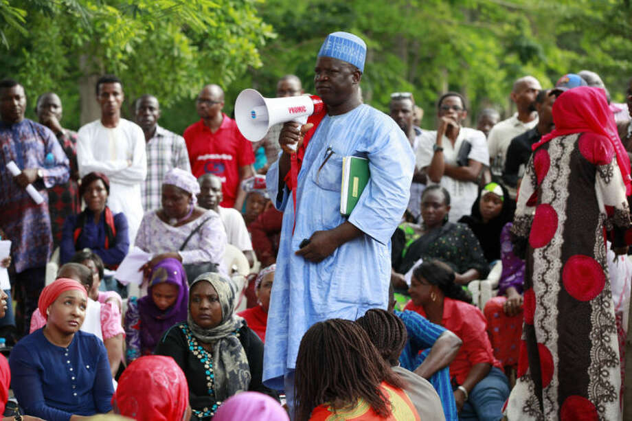 "Hosea Abana, centre, the chairman of the Chibok community in Abuja, pauses, during a rally calling on the Government to rescue the school girls kidnapped from the Chibok Government secondary school, in Abuja, Nigeria, Saturday May 10, 2014. The president of Nigeria for weeks refused international help to search for more than 300 girls abducted from a school by Islamic extremists, one in a series of missteps that have led to growing international outrage against the government. The waiting has left parents in agony, especially since they fear some of their daughters have been forced into marriage with their abductors for a nominal bride price of $12. Boko Haram leader Abubakar Shekau called the girls slaves in a video this week and vowed to sell them. ""For a good 11 days, our daughters were sitting in one place,"" said Enoch Mark, the anguished father of two girls abducted from the Chibok Government Girls Secondary School. ""They camped them near Chibok, not more than 30 kilometers, and no help in hand. For a good 11 days."" (AP Photo/Sunday Alamba)"