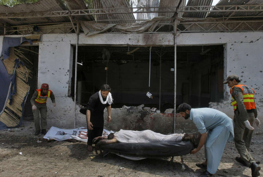 Pakistani volunteers and rescue workers remove a lifeless body from the site after a bomb explosion in Peshawar, Pakistan, Sunday, May 11, 2014. A police official in Pakistan says a bomb blast targeting refugees registering with the government has killed several people in northwestern city of Peshawar. Faisal Mukhtar says the bombing Sunday on a soccer field also wounded many people. He says it happened as officials registered refugees from the nearby Khyber tribal region. (AP Photo/Mohammad Sajjad)