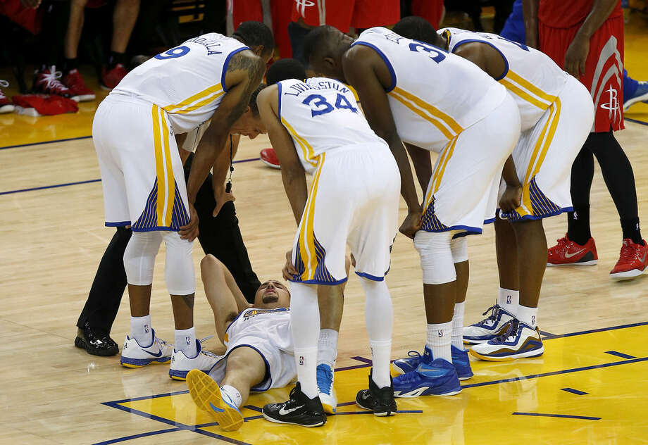 In this photo taken May 27, 2015, Golden State Warriors guard Klay Thompson, bottom, is checked on by teammates after taking a knee to his head from Houston Rockets forward Trevor Ariza during the second half of Game 5 of the NBA basketball Western Conference finals. The Warriors hope to get healthy and stay in tune over the next week before facing the Cleveland Cavaliers in the NBA Finals. Thompson needs to pass through the league's concussion protocol and Stepehen Curry is trying to get his aching body back at full strength. (AP Photo/Tony Avelar, File