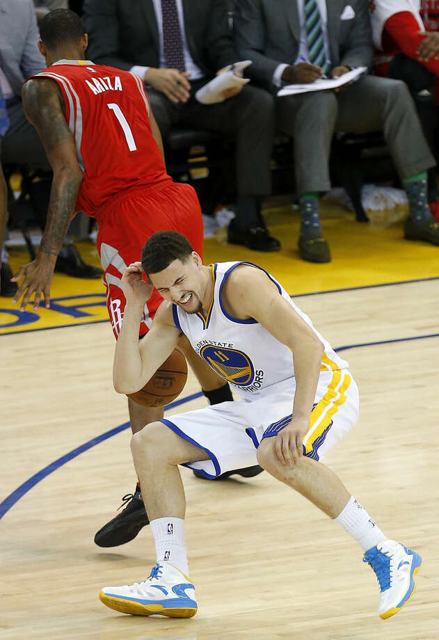 In this photo taken May 27, 2015, Golden State Warriors guard Klay Thompson (11) reacts after taking a knee to his head from Houston Rockets forward Trevor Ariza (1) during the second half of Game 5 of the NBA basketball Western Conference finals. The Warriors hope to get healthy and stay in tune over the next week before facing the Cleveland Cavaliers in the NBA Finals. Thompson needs to pass through the league's concussion protocol and Stepehen Curry is trying to get his aching body back at full strength. (AP Photo/Tony Avelar)