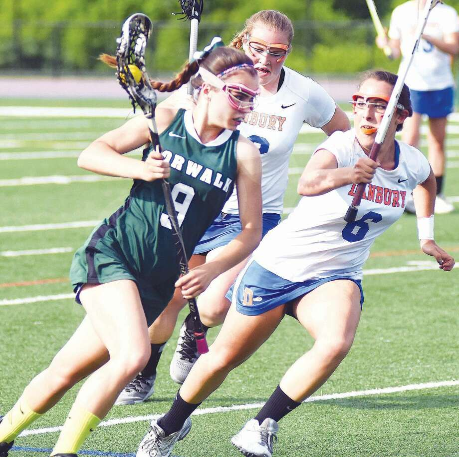 Hour photo/John Nash - Norwalk's Grace Bradley, left, drives past Danbury's Bianca Melillo during Friday's CIAC Class L preliminary game in Danbury.