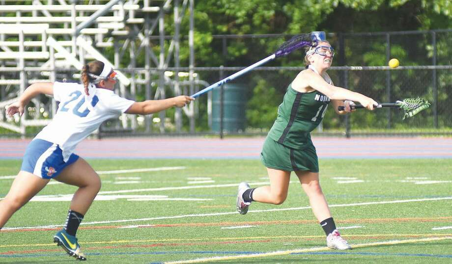Hour photo/John Nash - Norwalk's Kaitlin Uralowich, right, rips of a free-position shot as Danbury defender Laurie Stark moves in to defend during the first half of Friday's CIAC Class L preliminary playoff game.