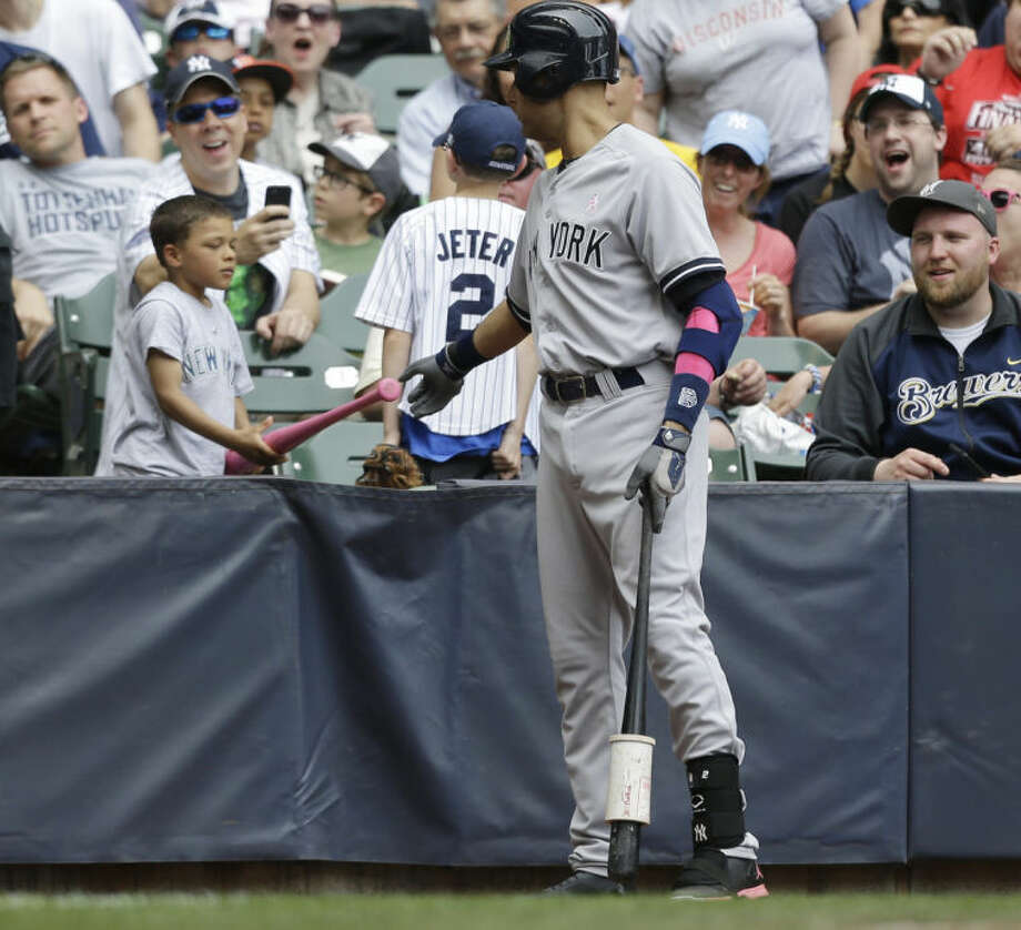 New York Yankees' Derek Jeter gives a pink bat to a small boy while waiting to bat in the fourth inning of a baseball game against the Milwaukee Brewers Sunday, May 11, 2014, in Milwaukee. (AP Photo/Jeffrey Phelps)