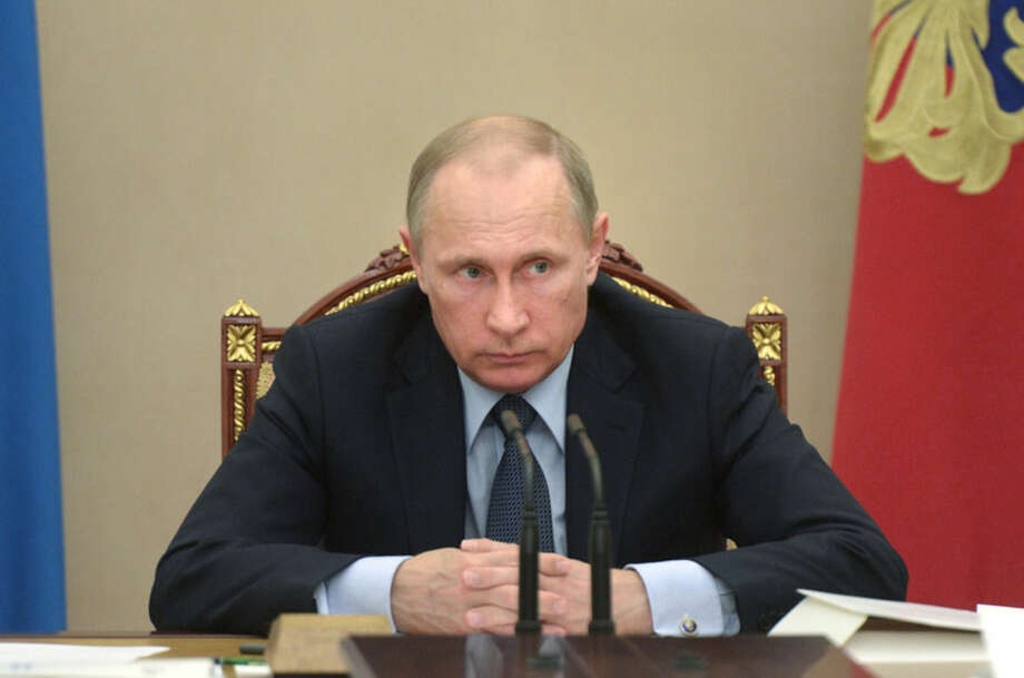"In this Wednesday, May 27, 2015 pool photo Russian President Vladimir Putin listens during a meeting in the Kremlin, Moscow, Russia. Putin says the United States is meddling in FIFA's affairs in an attempt to take the 2018 World Cup away from his country. Putin said in televised comments Thursday, May 28, 2015, that it is ""odd"" that the probe was launched at the request of U.S. officials for crimes which do not involve its citizens and did not happen in the United States. (Alexei Nikolsky/RIA Novosti, Kremlin Pool Photo via AP)"