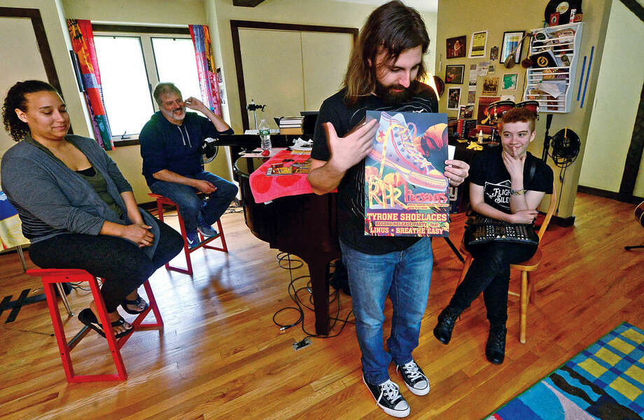 Chris Yerinides co-founder of RabbitHouse Records, a local record label from Norwalk, Conn. displays a promtional poster for the band, Tyrone Shoelaces, while bandmembers, Sarah Golley and Chuck Chesller and poster designer, Thomas Turner, right, look on Wednesday, May 18, 2016.