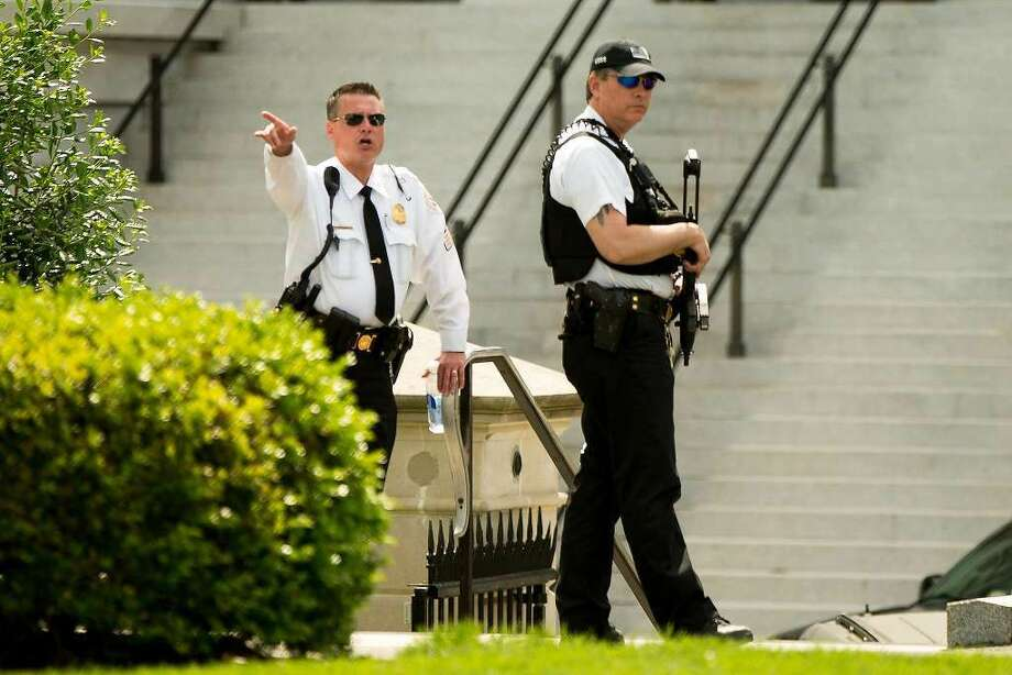 A Secret Service agent orders people into buildings near the entrance to the West Wing of the White House in Washington, Friday, May 20, 2016, after the White House was placed on security alert after shooting on street outside. (AP Photo/Andrew Harnik)