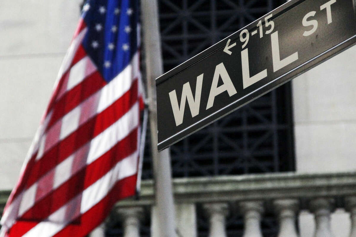 FILE - This Monday, July 15, 2013, file photo, shows the American flag and Wall Street street sign outside the New York Stock Exchange, in New York. Asian stock markets were mixed Monday, Sept. 29, 2014, as pro-democracy protests in Hong Kong and concern about China's economy offset good U.S. economic news. (AP Photo/Mark Lennihan, File)