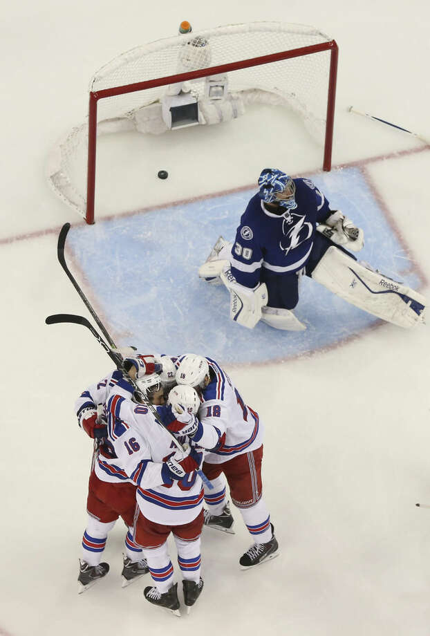 New York Rangers surround center J.T. Miller (10) after he scored against Tampa Bay Lightning goalie Ben Bishop (30) during the third period of Game 6 of the Eastern Conference finals in the NHL hockey Stanley Cup playoffs,Tuesday, May 26, 2015, in Tampa, Fla. The Rangers defeated the Lightning 7-3. (AP Photo/Chris O'Meara)