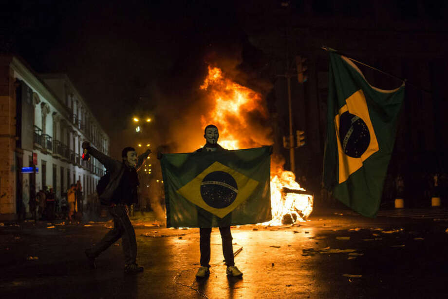 FILE - In this June 17, 2013, file photo, a demonstrator holds a Brazilian flag in front of a burning barricade during a protest in Rio de Janeiro. Brazil. In a poll last year, more than three-fourths of Brazilians said they're certain corruption has infused the World Cup. Their anger fueled widespread and often violent anti-government protests last June that sent more than 1 million Brazilians into the street during FIFA's Confederations Cup soccer tournament. (AP Photo/Felipe Dana, File)
