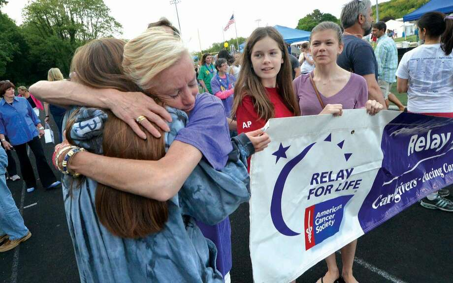 Hour Photo/Alex von Kleydorff. Cancer survivior Kelly Healy hugs her daughter and caregiver Caitlin as caregivers join survivors holding the banner for a lap around the Veterans Memorial Stadium field at the start of the American Cancer Society's 18th annual Wilton Relay for Life