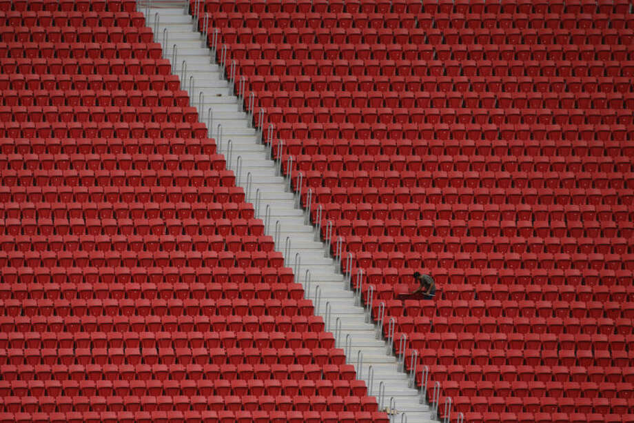In this April 8, 2014, photo, a worker is seen at the the Mane Garrincha stadium, in Brasilia, Brazil. Mane Garrincha stadium, which boasts 288 imposing concrete pillars holding aloft a high-tech self-cleaning roof, has become the costliest project related to Brazil's World Cup. Critics call it the poster child for out-of-control spending and mismanagement, or worse. (AP Photo/Eraldo Peres)