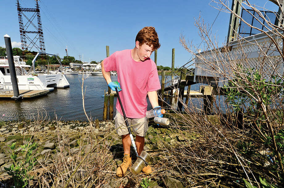 Hour photo / Erik Trautmann Paul Gelhaus, New Canaan High student & member of Maritime Rowing Club and Maritime Aquarium at Norwalk staff clean up litter along Norwalk River outside Aquarium Saturday.