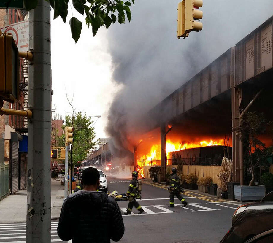 In this photo provided by Benjamin Parkin, firefighters battle a blaze at the Metro-North railroad tracks in New York, Tuesday, May 17, 2016. Train service into and out of Grand Central is being delayed due to the fire. (Benjamin Parkin via AP) MANDATORY CREDIT