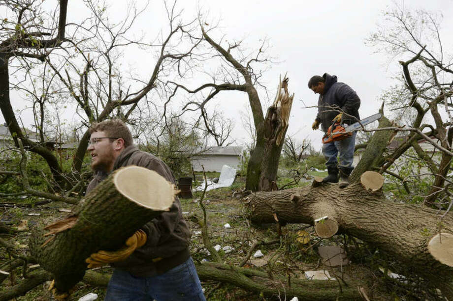 Adam Pankoke, left, and Nick Streit, clear fallen trees in Beaver Crossing, Neb., Monday, May 12, 2014. Beaver Crossing was hit hard after several tornadoes moved across Nebraska on Sunday causing damage to homes and businesses in or near Sutton, Garland, Cordova and Daykin. The storms also left more than 18,000 utility customers without electricity. (AP Photo/Nati Harnik)