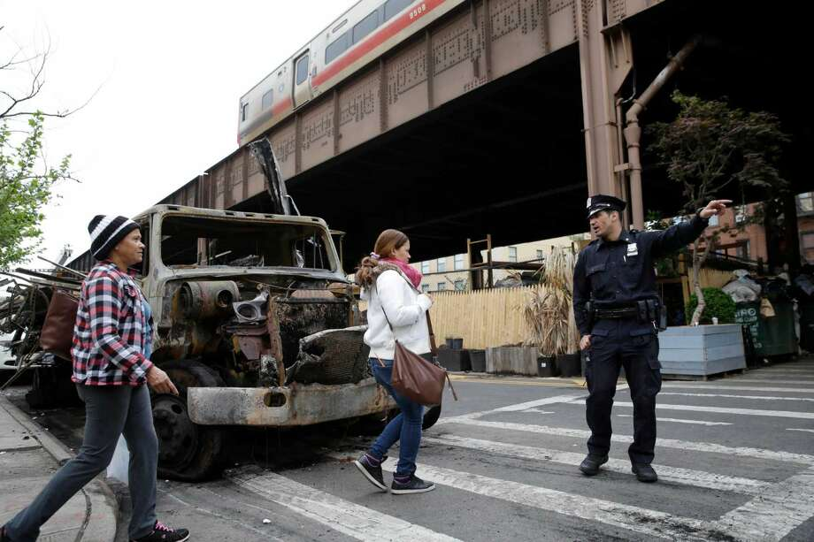 As a Metro-North train passes over, a police officer directs pedestrians around the site of an extinguished fire in New York, Wednesday, May 18, 2016. Commuters into and out of New York's famed Grand Central Terminal faced crippling delays Wednesday, a day after a raging fire broke out beneath elevated train tracks in the city, officials said.