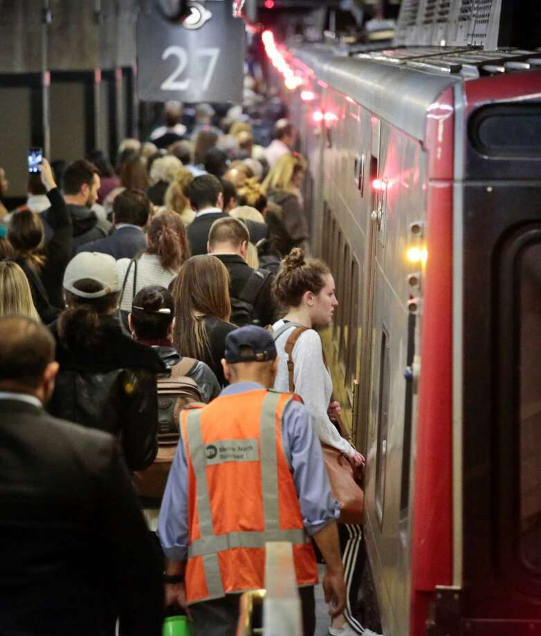 Passengers board a Metro-North train at Grand Central Terminal, Wednesday, May 18, 2016, in New York. Commuters into and out of terminal faced delays, a day after a fire broke out beneath elevated train tracks in the city.