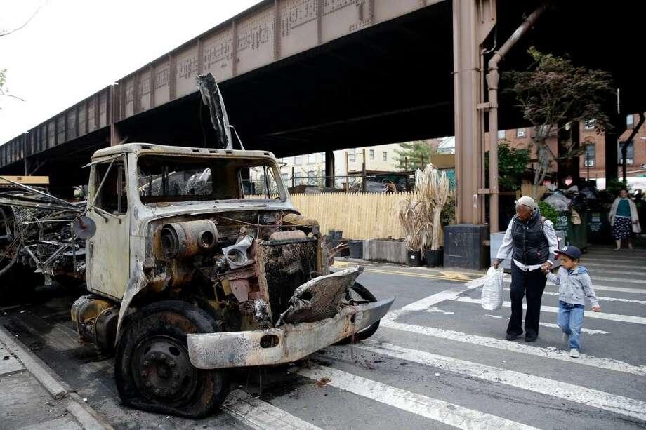 Pedestrians look at a burnt out truck at the site of a fire underneath Metro-North train tracks in New York, Wednesday, May 18, 2016. Commuters into and out of New York's famed Grand Central Terminal faced crippling delays Wednesday, a day after a raging fire broke out beneath elevated train tracks in the city, officials said. Metro-North said two of the four tracks in the area of the fire were operational for Wednesday's morning rush.