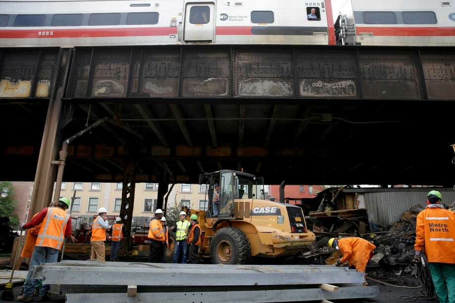 While a Metro-North train passes above, work continues underneath the tracks at the site of a fire in New York, Wednesday, May 18, 2016. Commuters into and out of New York's famed Grand Central Terminal faced crippling delays Wednesday, a day after a raging fire broke out beneath elevated train tracks in the city, officials said. Metro-North said two of the four tracks in the area of the fire were operational for Wednesday's morning rush.