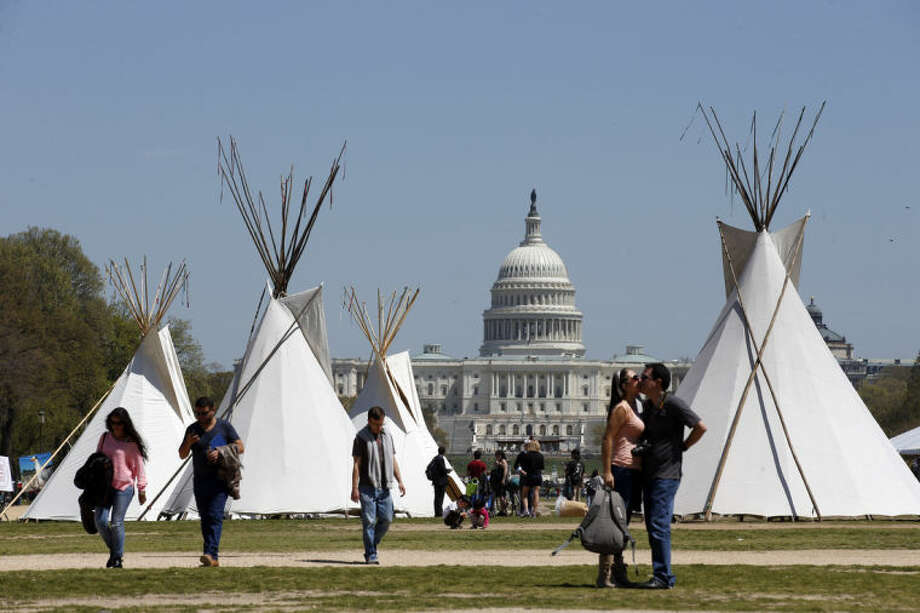 FILE - In this April 21, 2014, file photo, people walk near teepees set up on the National Mall in Washington, looking toward the Capitol. Days after President Barack Obama touted executive actions aimed at increasing energy efficiency, a bill with similar goals is expected to fall victim to partisan gridlock in the Senate. A bipartisan bill to promote many of the same efficiency goals Obama touted May 9 in California is expected to go down in defeat May 12 amid a dispute over the Keystone XL oil pipeline. (AP Photo/Alex Brandon, File)